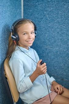 Pacjentka uśmiecha się do kamery podczas badania słuchu