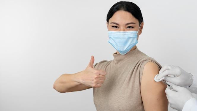 Pacjentka w masce medycznej pokazująca kciuk w górę, gdy dostaje zastrzyk ze szczepionki