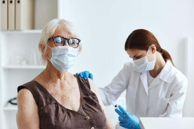Pacjentka w podeszłym wieku obok paszportu lekarza covid