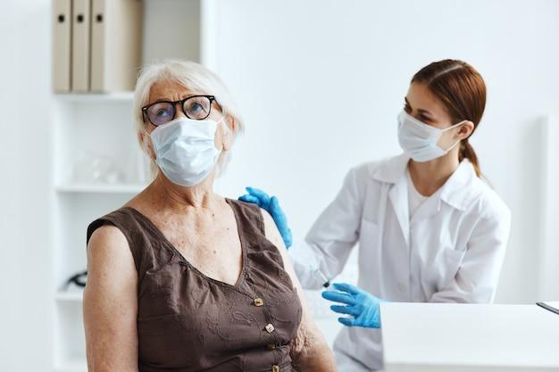 Pacjentka w podeszłym wieku obok paszportu ze szczepionką lekarza