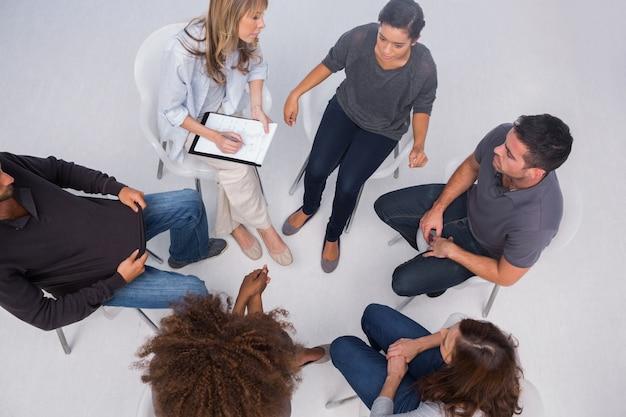 Pacjentów słuchających siebie w sesji grupowej siedzi w kole