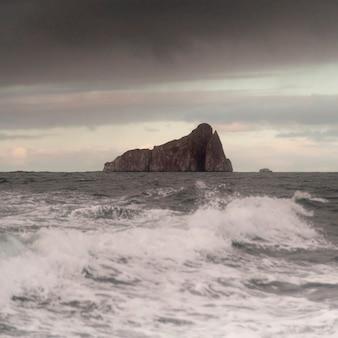 Pacyficzny ocean z kopacz skałą w tle, san cristobal wyspa, galapagos wyspy, ekwador