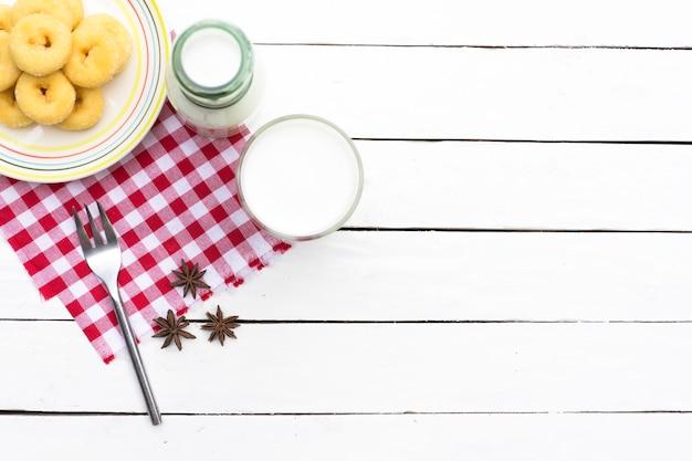 Pączek deser i butelki mleka i szkła mlecznego na czerwoną kratkę tkaniny