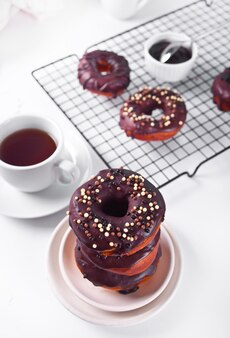 Pączek glazurowany kremem czekoladowym lub lukrem i filiżanką kawy. koncepcja śniadanie.