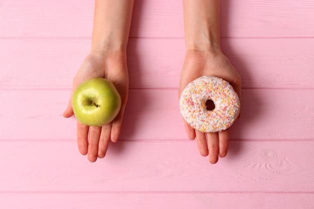 Pączek i jabłko w kobiecych rękach zdrowy i niezdrowy wybór żywności