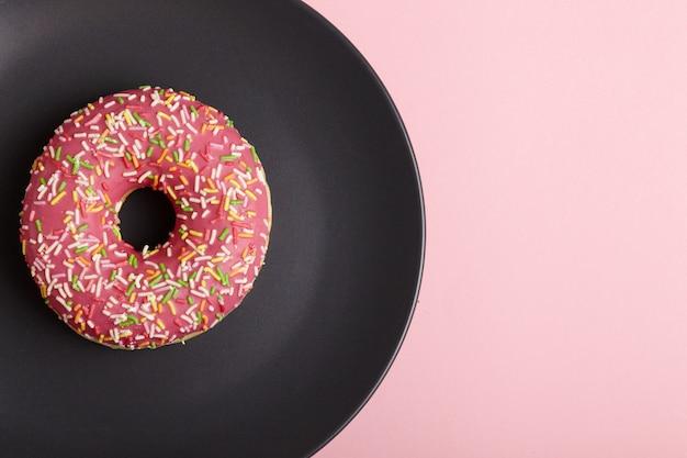 Pączek na czarnym talerzu na pastelowym różowym tle.