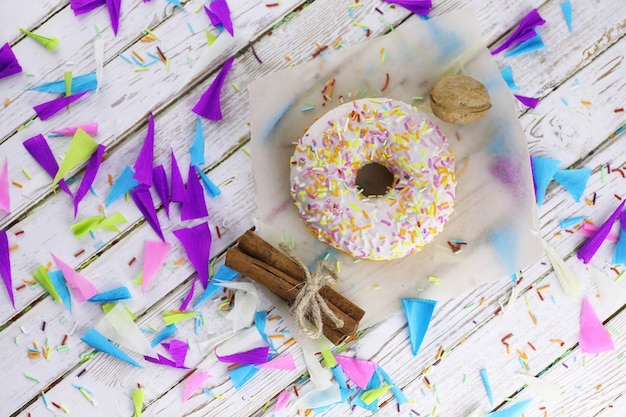 Pączek na drewnianym białym tle i rozrzucone słodkie ozdoby