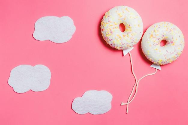 Pączek na różowo, kreatywny minimalizm żywności, pączek w kształcie balonu na niebie z chmurami, widok z góry z miejsca na kopię, stonowany