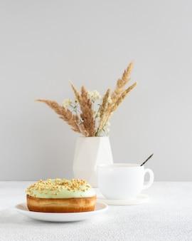 Pączek Pistacjowy I Filiżanka Kawy Na Stole Z Suszonymi Kwiatami W Małym Minimalistycznym Wazonie Premium Zdjęcia