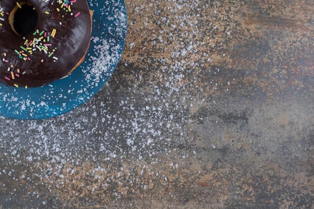 Pączek posypany cukierkami i polewą czekoladową wystawiony na marmurowej powierzchni
