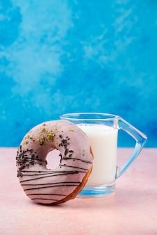 Pączek truskawkowy z dekoracjami i szklanką mleka na różowym stole.