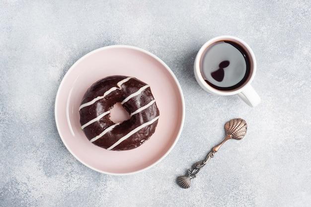 Pączek w glazurze i filiżankę kawy na stole