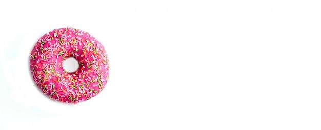 Pączek w różowej polewie z wielokolorową posypką na białym tle.