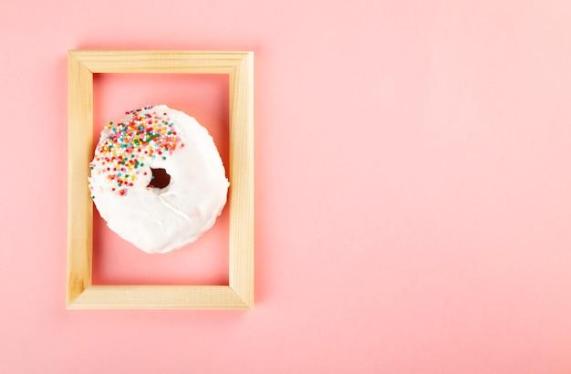 Pączek z białym lukrem i wielobarwny cukru polewa w drewnianej ramie na różowym tle. widok z góry. skopiuj miejsce