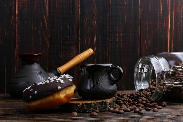 Pączek z czarnym lukrem i czekoladą w proszku oraz autentyczny kubek mocnej kawy. puszka ziaren kawy i nalane ziarna.