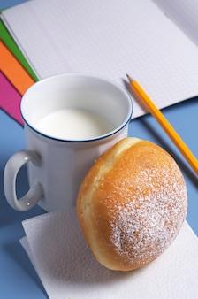 Pączek z kubkiem mleka i zeszytami szkolnymi na biurku