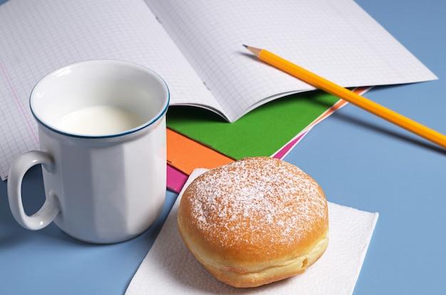 Pączek z kubkiem mleka i zeszytami szkolnymi na stole
