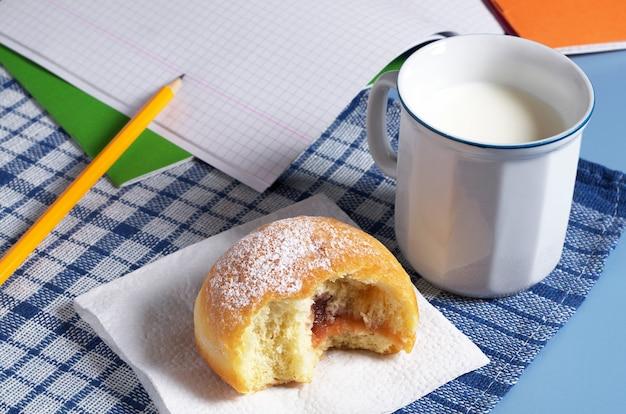 Pączek z kubkiem mleka i zeszytem szkolnym na stole