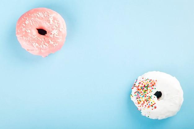 Pączek z polewą białą i różową oraz wielobarwną cukrową polewą na niebieskim tle. widok z góry. skopiuj miejsce