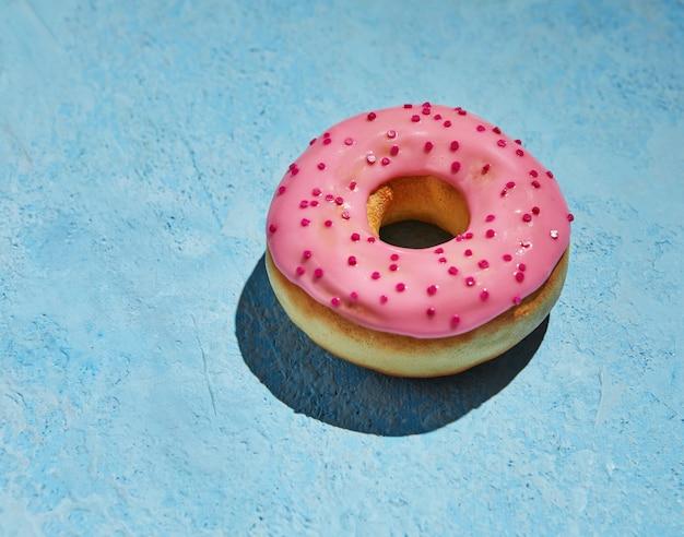 Pączek z różowym lukrem i posypką na niebieskim tle.
