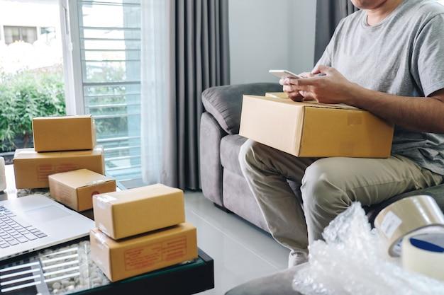 Paczka dla małych firm do wysyłki do klienta w domu, młody przedsiębiorca mśp niezależny człowiek pracujący w biznesie online za pomocą smartfona przy składaniu zamówienia i przygotowywaniu produktu paczkowego