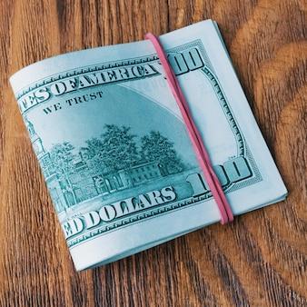 Paczka dolarów związana gumką leży na drewnianych deskach.