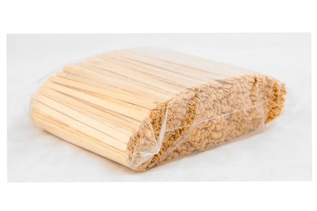 Paczka drewnianych patyczków do mieszania na białym tle