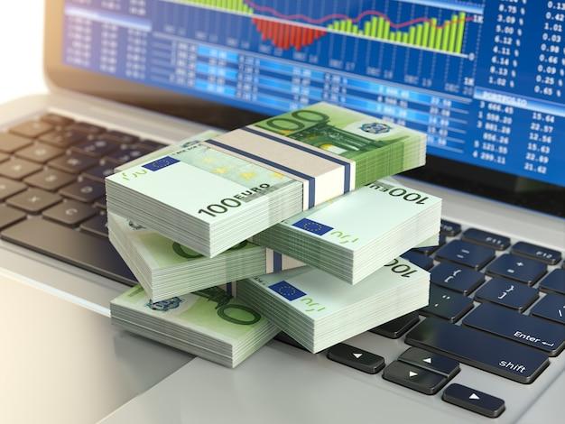 Paczka euro na klawiaturze laptopa z wykresem giełdowym na ekranie