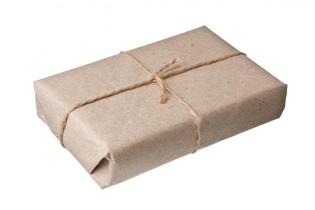 Paczka owinięta brązowym papierem pakowym na białym tle