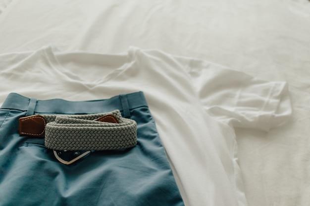 Paczka ubrań na białym łóżku z białą niebieską koszulką i paskiem do ubrania.