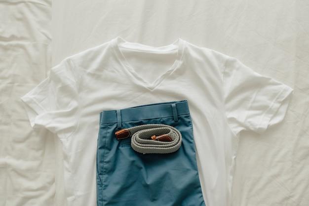 Paczka ubrań na łóżku z białą niebieską koszulką krótką i paskiem do ubrania.