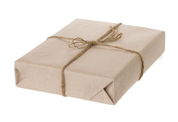 Paczka zawinięta i papier związany liną na białym tle