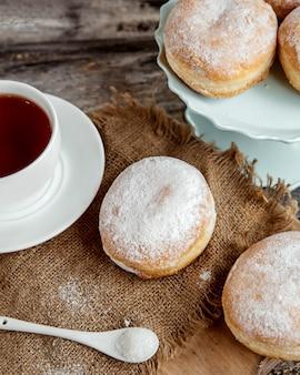 Pączki budyniowe zasilane cukrem podawane z czarną herbatą