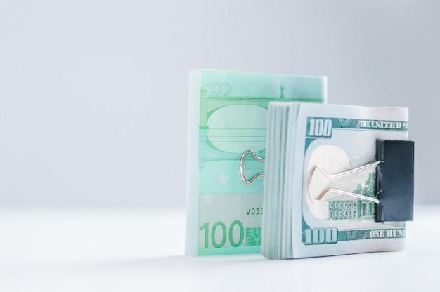 Paczki euro i banknotów stu dolarowych leżą na białym stole, spięte spinaczami. pojęcie oszczędności w czasie kryzysu