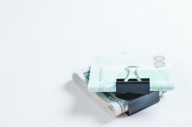 Paczki euro i studolarowych banknotów leżą na białym stole spiętym spinaczami. pojęcie oszczędności w czasie kryzysu. dolary kontra euro. różne środki przekazu