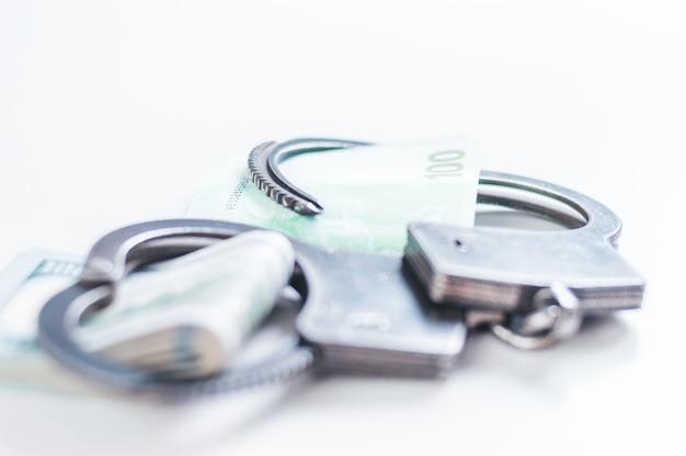 Paczki euro i studolarowych banknotów są zamknięte w bransoletkach kajdanek. pojęcie kradzieży, oszustwa i nielegalnego biznesu. korupcja. różne środki przekazu