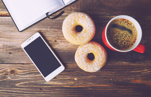 Pączki i kawa leżące na rustykalnym drewnianym tle z otwartym notatnikiem i widokiem z góry na telefon komórkowy