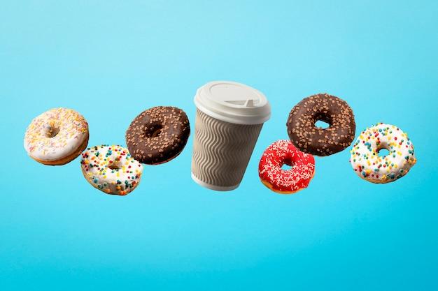 Pączki latające w powietrzu i papierowy kubek kawy na niebiesko. piekarnia, koncepcja pieczenia.