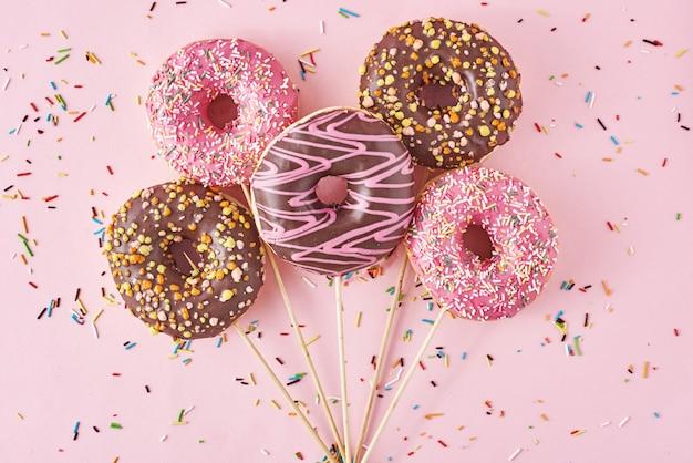 Pączki na różowym tle z konfetti. kreatywny styl minimalizmu żywności