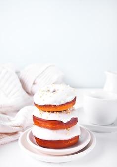 Pączki na talerzu glazurowanym kremem z białej czekolady lub lukrem i butelką z mlekiem w tle.