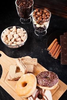 Pączki, orzeszki ziemne w czekoladzie i ziarnach kawy na drewnianym tle