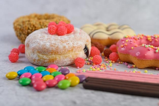Pączki posypane cukrem pudrem i słodyczami na białej powierzchni.