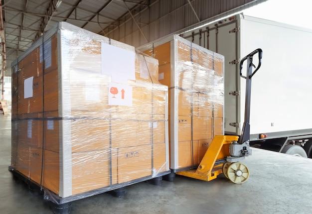 Paczki ułożone na stosie na regale paletowym, czekające na załadowanie do kontenera transportowego pudła transportowe