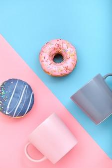 Pączki z polewą i filiżanki do kawy na pastelowej niebiesko-różowej powierzchni, słodkie pączki.