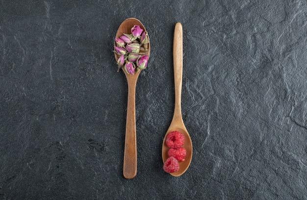 Pączkujące róże i maliny na drewnianych łyżkach.