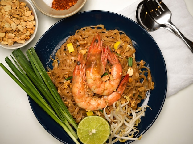 Pad thai, makaron tajski opalany z krewetkami podany na stole z limonką, kiełkami fasoli i szczypiorkiem, widok z góry