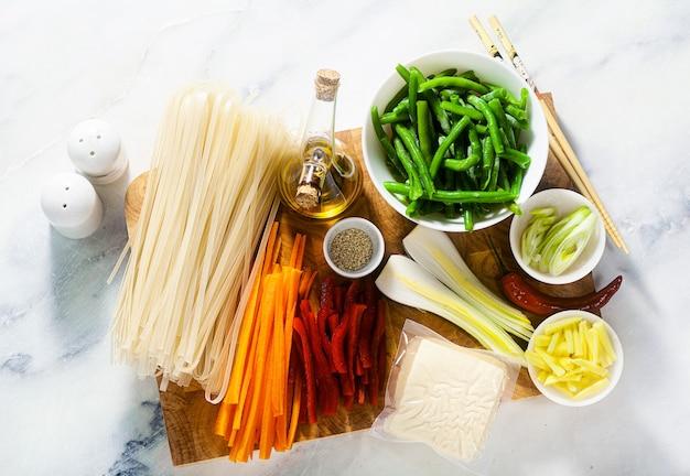Pad thai składniki na desce do krojenia na stole z białego marmuru