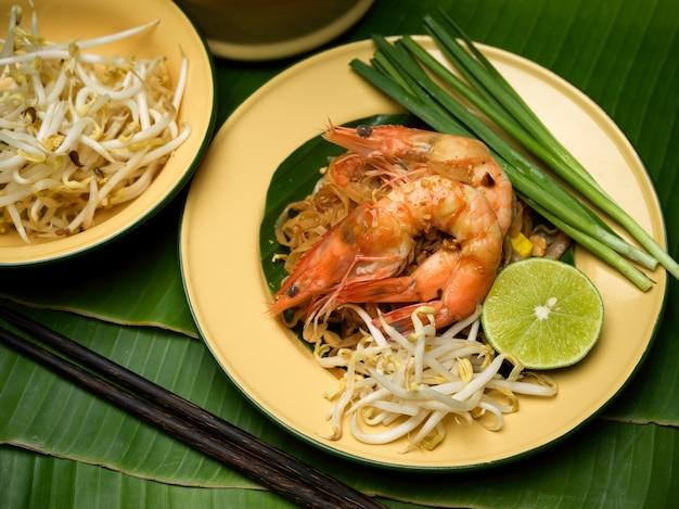 Pad thai, tradycyjne tajskie jedzenie, tajski makaron z mieszanką krewetek podawany na tradycyjnym talerzu z limonką, kiełkami fasoli i szczypiorkiem