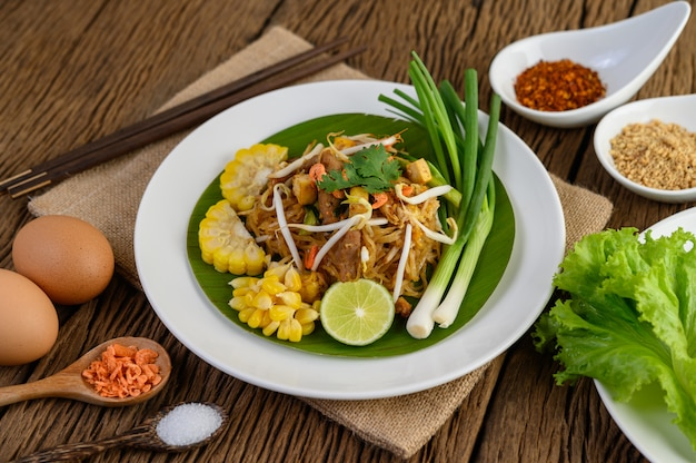 Pad thai w białym talerzu z cytryną, jajkami i przyprawami na drewnianym stole.