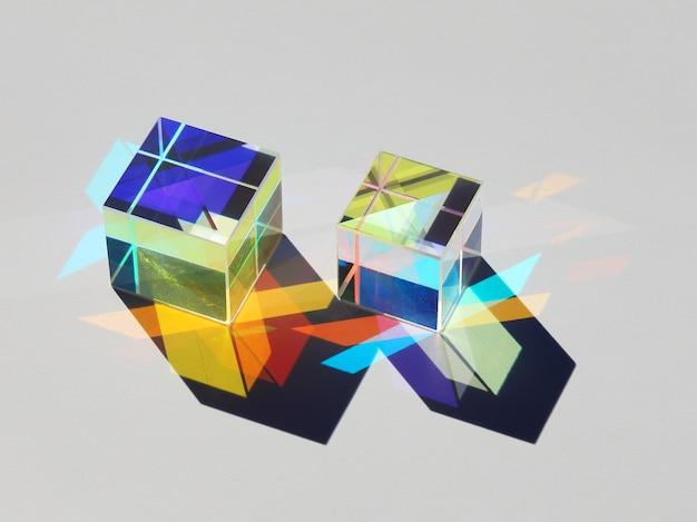 Padający cień dwóch szklanych kostek z wieloma kolorowymi promieniami